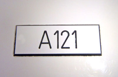 Fräst Litteraskylt 40x15x1,6mm. Vit m svart text, häftäm, ej hål